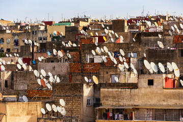 FES, MOROCCO - November 16, 2018: Great amount satellite dishes of parabolic antennas on building roofs of the old medina in Fes, Morocco, Africa