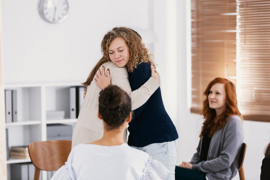 Two woman comforting each other during group psychotherapy for abuse victims