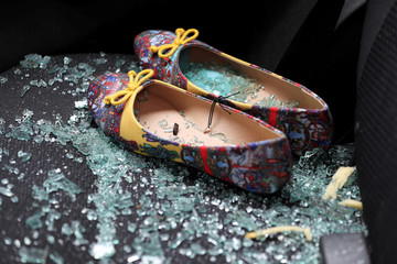 Shattered glass covers shoes left on the seat of a car that was damaged after a rocket hit a house north of Tel Aviv, Israel
