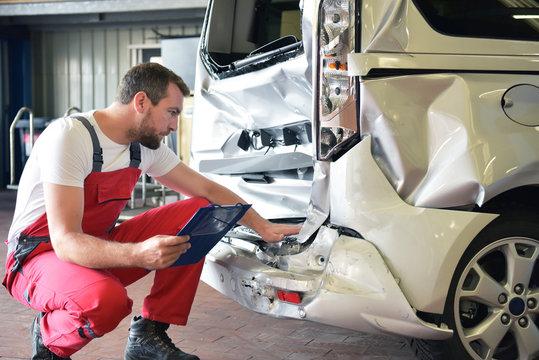 Begutachtung Unfallwagen in einer Autowerkstatt durch Mechaniker // Inspection of accident vehicles in a garage by a mechanic