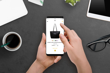 Female buys a bag online with her smartphone. Online shopping concept
