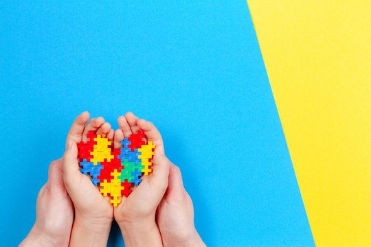 Adult and kid hands holding colorful heart on yellow and blue background. World autism awareness day concept