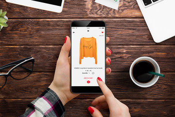 Female hands in office buying yellow hoodie online on her smartphone, surrounded with office supplies