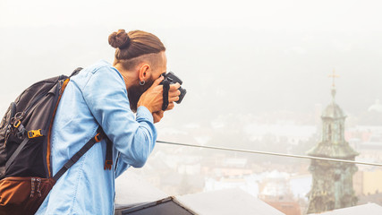 Traveler Young Man with a Beard Photographs Attractions and Panorama of the Ancient City from a High Observation Platform. Travel Tourism Concept