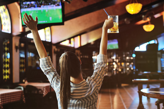 young pretty girl football fan with a glass of beer in hands watching football in the sports bar