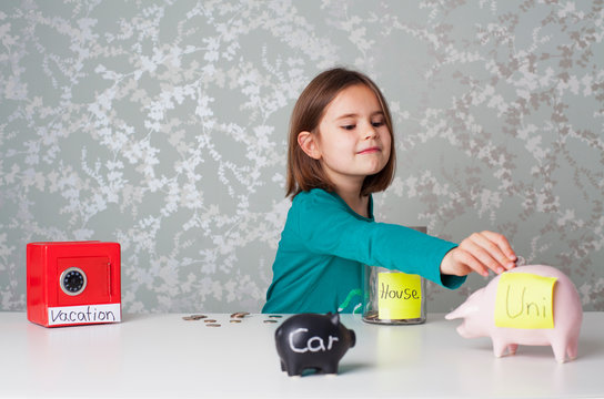 Pre teen caucasian girl putting a going into a piggy bank surrounded by piggy banks and money boxes