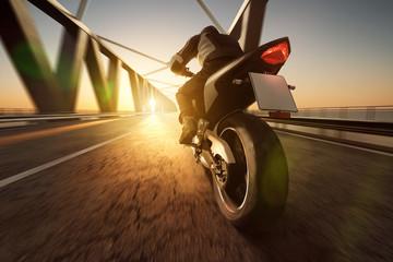 Wall Mural - Motorrad fährt über Brücke im Sonnenuntergang
