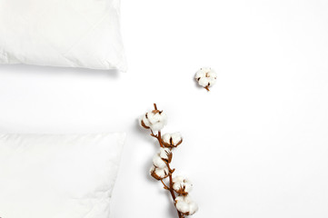 Soft white quilted pillow and branch of cotton on light background top view. Clean pillow, interior item, bedding mockup design template