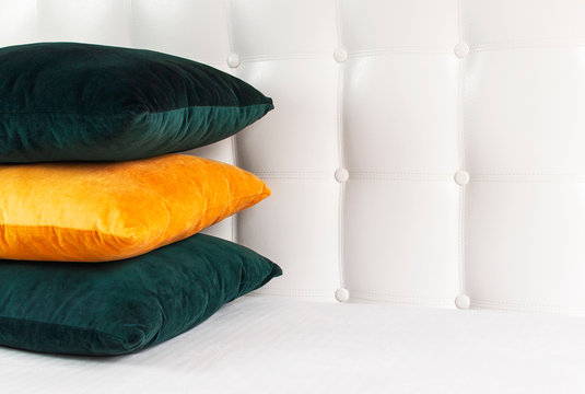 Bright decorative soft pillows in bed on the background of leather quilted headboard. Emerald and orange pillow, part of bed close-up, comfort. Quilted headboard background, interior