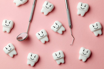 Healthy white teeth are smiling on pink background and dentist tools mirror, hook.
