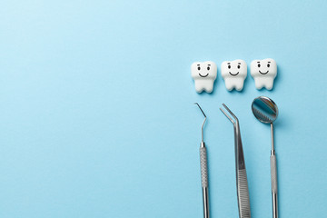Healthy white teeth are smiling on blue background and dentist tools mirror, hook. Copy space for text.