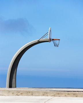 Basketball hoop and backboard against blue sky