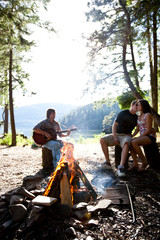 Young adults camping sit around a fire next to Lake Pend Oreille in Sandpoint, Idaho.