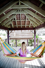 A girl relaxes on a porch in a hammock  with her back to the camera and arms out.