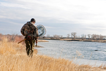 A man searcher for trout while walking along a river.