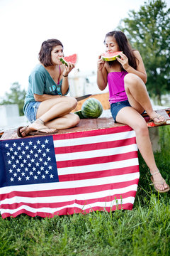 Two sisters eat watermelon on flatbed truck
