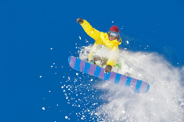 Jumping snowboarder with clouds of snow.