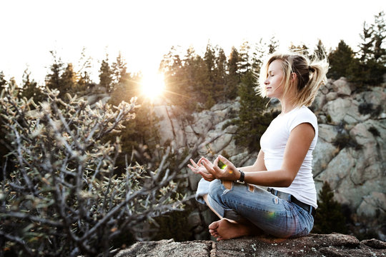 Young woman meditating on cliff at sunset