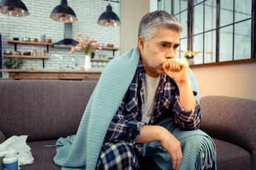 Unhappy ill man having a strong cough