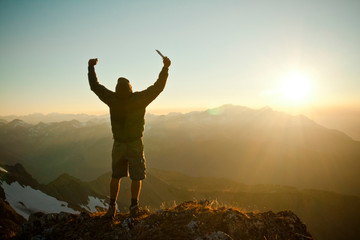 A hiker stands on the summit of Crystal Peak and raises his knife in the air as the shine beams illuminate the landscape.