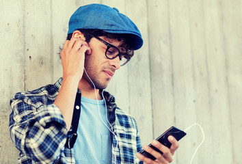people, music, technology, leisure and lifestyle - happy young hipster man with earphones and smartphone listening to music