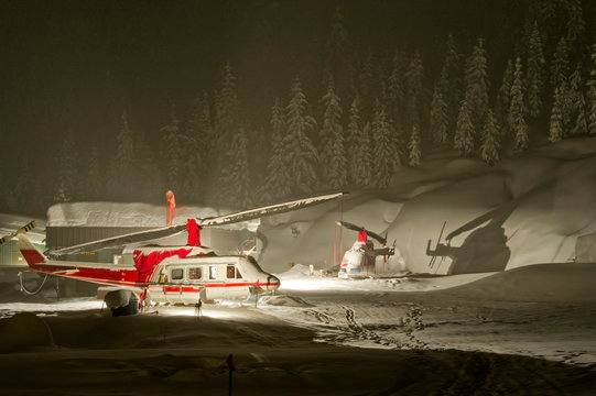 Bell 212 and 206 helicopters used for heli-skiing parked in heavy snowfall in Canada.