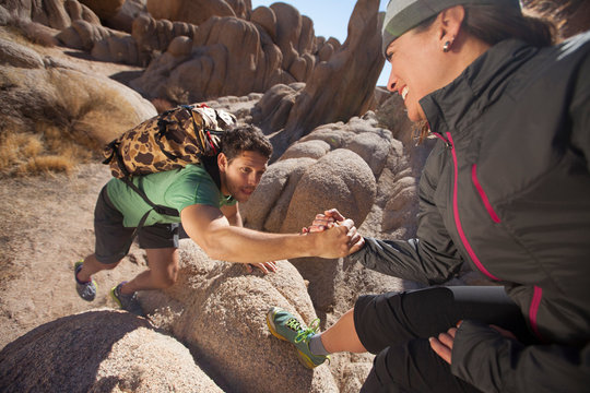 A man and woman helping each other up onto boulders in the desert.