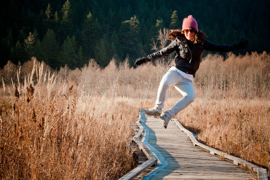 A young woman jumping and heel clicking while walking along a boardwalk at One Mile Lake near Pemberton, British Columbia, Canada.