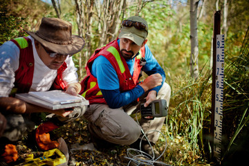 Two scientist collect data at a stream gauge in the field.