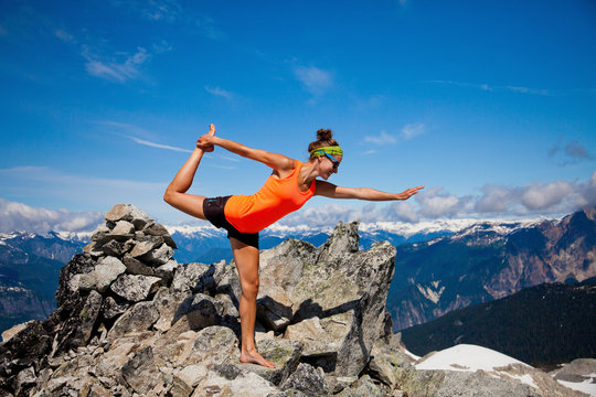 Young woman practices Yoga on mountain summit