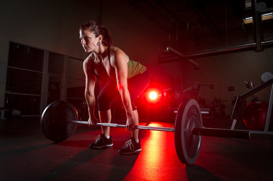 Crossfit trainer Michelle set to lift the barbell during a routine at a local fitness gym in Valencia CA.