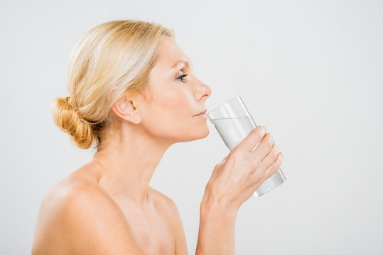 side view of mature woman drinking water from glass isolated on grey
