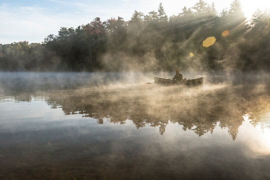 Man fishes amongst the early morning fog on a lake in Vermont.