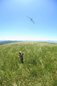 Young boy flies a toy glider airplane in the open fields along the Appalachian Trail atop Max Patch Bald west of Asheville, NC