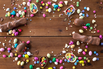 easter, sweets and confectionery concept - chocolate eggs, bunnies and candy drops on wooden background