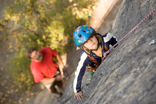 Young girl (age 5) climbing on granite cliff  while father belays and watches, Stone Hills near Rexford, Montana.