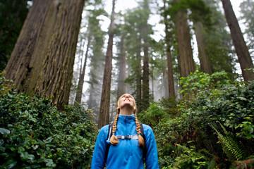 Woman in blue fleece hiking in lush green forest