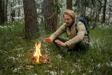 Man sitting next to campfire