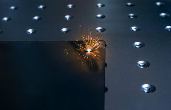 Closeup laser engraver working and engraving flat metal surface