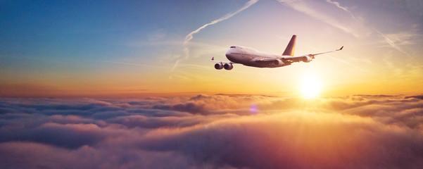 Türaufkleber Flugzeug Commercial airplane flying over dramatic sunset
