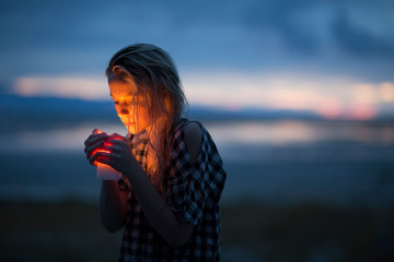 A young woman with a candle stands in the desert.