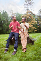 Two men leaning against picnic table and talking