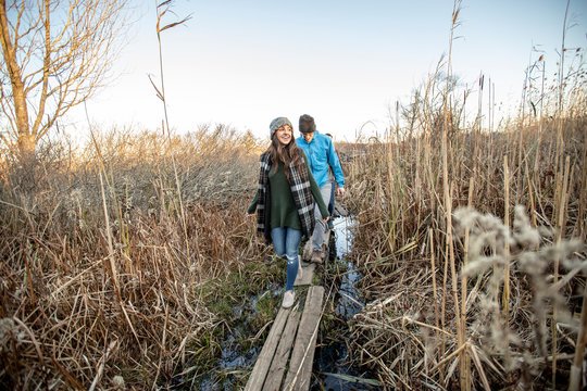 Woman and man walking on plank through reeds