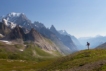 A male hiker is looking over the Val Veny, near Courmayeur, with Mont Blanc dominating the sky line.