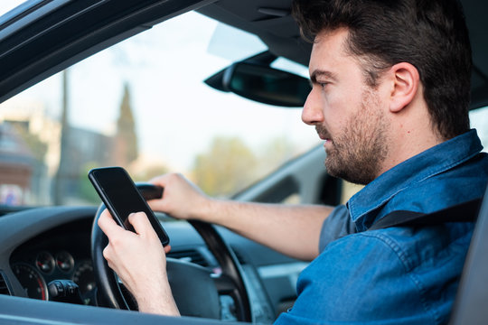 Male in car using mobile phone at the wheel