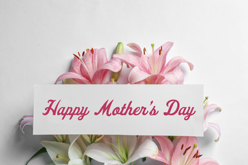 Composition with beautiful blooming lily flowers and card on white background