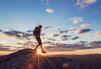 Silhouette of female hiker at summit of Borestone Mountain at sunset, Maine, USA
