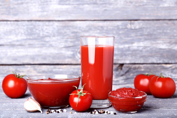 Wall Mural - Tomato juice in glass with ketchup and garlic on wooden table