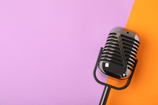 Retro microphone on color background, top view with space for text