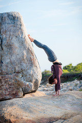 Woman doing yoga handstand on rock